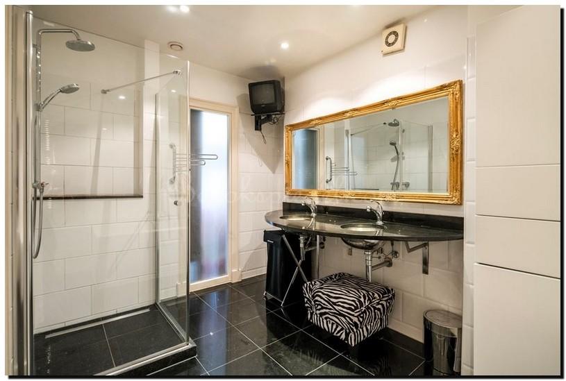 gouden barok spiegel in zwart wit badkamer